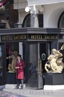 The bellhop waits outside the entrance to the Hotel Sacher in Vienna, Austria to assist guests with their luggage or transportation.