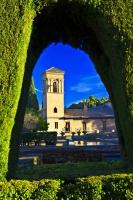 The unique architecture of the Hotel San Francisco as seen through a rounded arch in the hedge in the City of Granada in Andalusia, Spain.