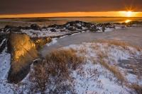 The picturesque scenery of the rocky coastline of the Hudson Bay in Churchill, Manitoba during a spectacular winter sunset.