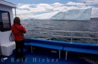 A large iceberg sits in the waters of the Great Northern Peninsula of Newfoundland, Canada as a woman snaps a picture from a Northland Discovery Boat Tour.
