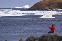 A woman sits on the rocky shore in the town of Quirpon on the Great Northern Peninsula of Newfoundland as she spends her time iceberg watching.