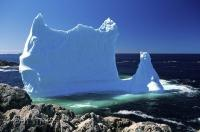 The remains of an iceberg, a high column of ice with a wide base is beached along the Newfoundland coast at Twillingate.