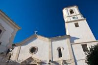 The White walls of the Iglesia de Santa Maria in Sorbas, Province of Almeria in Andalusia, Spain stand out with clean lines against the Spanish blue sky.