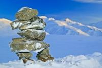 A collection of flattish rocks are stacked in the form of a human called an inukshuk, backdropped by the snow covered Brooks Range in Alaska.