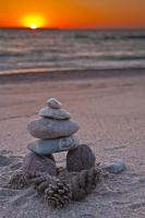 As sunset closes in around Agawa Bay in Lake Superior Provincial Park in Ontario, Canada, an Inukshuk decorates the coastline.