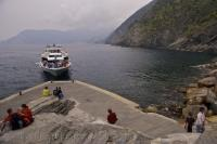 A small passenger ferry transports visitors between the villages of the Cinque Terre in Liguria, Italy with this trip arriving in the harbour of Vernazza.