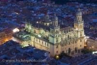 This sixteenth century cathedral that is lit up at dusk is the Jean Cathedral Church Building located in the Province of Jaen in Andalusia, Spain. The bright white lights make this building stand out against the darkened streets around.