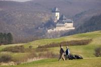 A twosome walks the Karlstein Golf Course in the Czech Republic while enjoying the scenery of the Karlstein Castle.