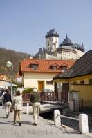 Tourists stroll through the village of Karlstein in the Czech Republic with the Karlstein Castle towering above them.