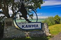 The welcome sign to the town of Kawhia, New Zealand with a beautiful scenic view of the harbour in the backdrop.