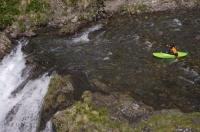 A kayaker prepares for his descent over the Sauth deth Pish on a kayaking adventure in the Val d'Aran in the Pyrenees in Catalonia, Spain.