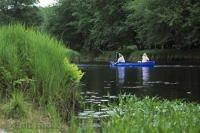 A couple enjoy a peaceful canoe on the Mersey River of Kejimkujik Park in Nova Scotia, Canada.