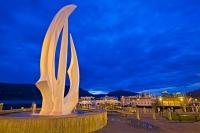 The Kelowna Sails sculpture and fountain is lit up at twilight in City Park along the Okanagan Lake waterfront in Kelowna British Columbia.