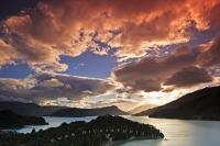 Dramatic clouds highlighted by sunset, hover above Kenepuru Sound in Marlborough Sounds, New Zealand. Kenepuru Sound is the second largest sound in Marlborough, a region situated at the top of the South Island of NZ.
