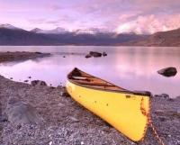 A serene scene of a yellow canoe hauled out onto the shore of Kluane Lake backdropped by snowcapped mountains during sunset in the Yukon Territory of Canada.
