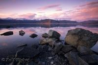 A flat calm Kluane Lake with beautiful sunset reflections in the clouds above.