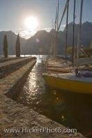 The sunlight shines off the sailboats tied up along the Lake Garda waterfront in the town of Torbole in the Province of Trento, Italy in Europe.