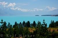 The scenery is stunning as you stand above the green landscape overlooking Lake Pukaki, Mt Cook and the Southern Alps on the South Island of New Zealand.