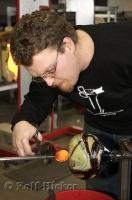 A glass blowing artist prepares to attach the vase to another pole at the Lincoln City Glass Center.