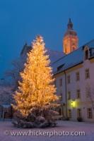 On the grounds of the Landratsmat in Neustift, Freising in Bavaria, Germany, a large Christmas tree is lit and highlights the area in yellow and golden hues.