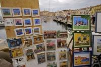 The local talent of the artists of Saint Tropez in Provence, France can be seen along the Quai Suffren in the Old Town where many visitors come to enjoy the beautiful scenery.
