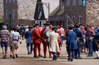 Tourists wander through the Quay at the Fortress of Louisbourg in Cape Breton, Nova Scotia where they are surrounded by costumed interpreters.