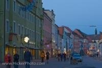 Even as dusk falls, the shops along the main street, Untere Haupstrasse, in Freising, Bavaria in Germany still attract the people strolling by.