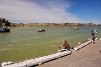 A popular pastime for locals in the town of Mangonui in Northland, NZ is to sit on the wharf casting fishing line out over the water on a warm summer day.
