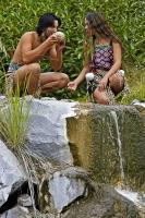 Maori people, a maiden and a warrior, crouch beside a waterfall while drinking from a conch shell at the Wairakei Terraces in New Zealand.