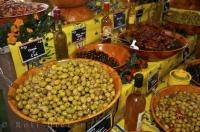 A large selection of marinated black and green olives, and sun dried tomatoes on display on the tables at the weekly market held in the quaint village of Moustiers Ste Marie in the Provence region of France.
