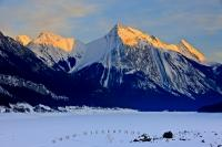 Medicine Lake is covered in snow during winter, while the sunset glows on the snow capped mountain peaks which surround it and the beautiful scenery of Jasper National Park in Alberta, Canada.