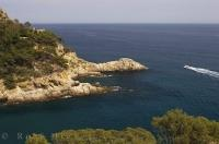 A boat cruises the Mediterranean Sea as it passes a bay along the coastline of the Costa Brava in Catalonia, Spain in Europe.