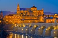 The Mezquita, also known as the Cathedral Mosque is the main tourist attraction in the city of Cordoba, in the foreground of this picture taken at dusk, is the famous Puento Romano bridge, Andalusia, Spain.