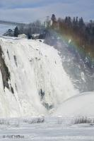 A rainbow forms in the mist created from the small stream of water plunging over the Montmorency Falls.