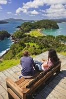 A couple sits on the bench enjoying the scenery of Motuarohia Roberton Island on the North Island of New Zealand.