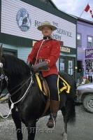 A RCMP Mountie dressed in full uniform on horseback at the Klondike Gold Rush National Historic Site, Dawson City, Yukon Territory, Canada.