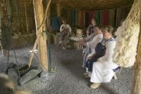 Women interpreters dressed in Viking costumes gather in a replica of an old viking hut with earthen floors to depict the history of vikings. This room was where woman gathered for sewing, weaving, and spinning as well as for socializing.