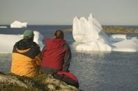 Honeymoon destinations showing a young couple in Newfoundland looking at Icebergs.
