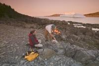 A couple of campers on vacation cooking up a meal on the shore in Newfoundland, Canada.