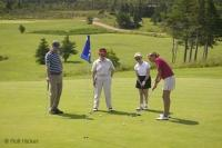 A foursome on vacation playing a round of golf at St. Andrews Na Creige Golf Course in Newfoundland, Canada.