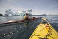 Stock Photo of sea kayaking around an large iceberg