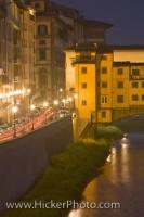 The night lights glisten along a street that runs along the riverside near the Ponte Vecchio in the City of Florence in the Region of Tuscany in Italy, Europe.