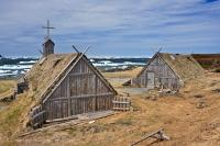 Recreated huts and buildings stand in the Norstead Viking Village along the Great Northern Peninsula of Newfoundland, Canada with pack ice floating in the harbour in the background.
