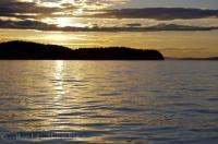 A picture of beauty, is a sunset over the waters off Northern Vancouver Island in British Columbia, Canada when the area becomes very tranquil as the lighting reflects off the calm waters.