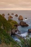 Rocks or nuggets arise from the waters beyond Nugget Point along the Southern Scenic Route in Otago, New Zealand.
