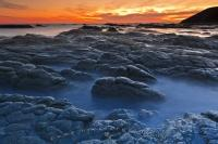 The Kaikoura Peninsula features a dramatic rocky landscape which fringes the waters of the Pacific Ocean in Canterbury, New Zealand. A beautiful time to visit this area of the peninsula is at sunset.