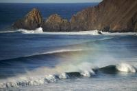 The Pacific Ocean rolls in with rainbow tipped waves along the Oregon Coast, USA.
