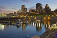The night lights along the Old Port and downtown Montreal, Quebec begin to sparkle as the enlightened sky at sunset starts to darken.