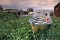 An old fishing boat rests on the shores in the L'Anse aux Meadows fishing village in Newfoundland, Canada.