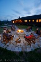 People gather around the outdoor fire pit at the Rifflin'Hitch Lodge along the Eagle River in Southern Labrador, Canada.